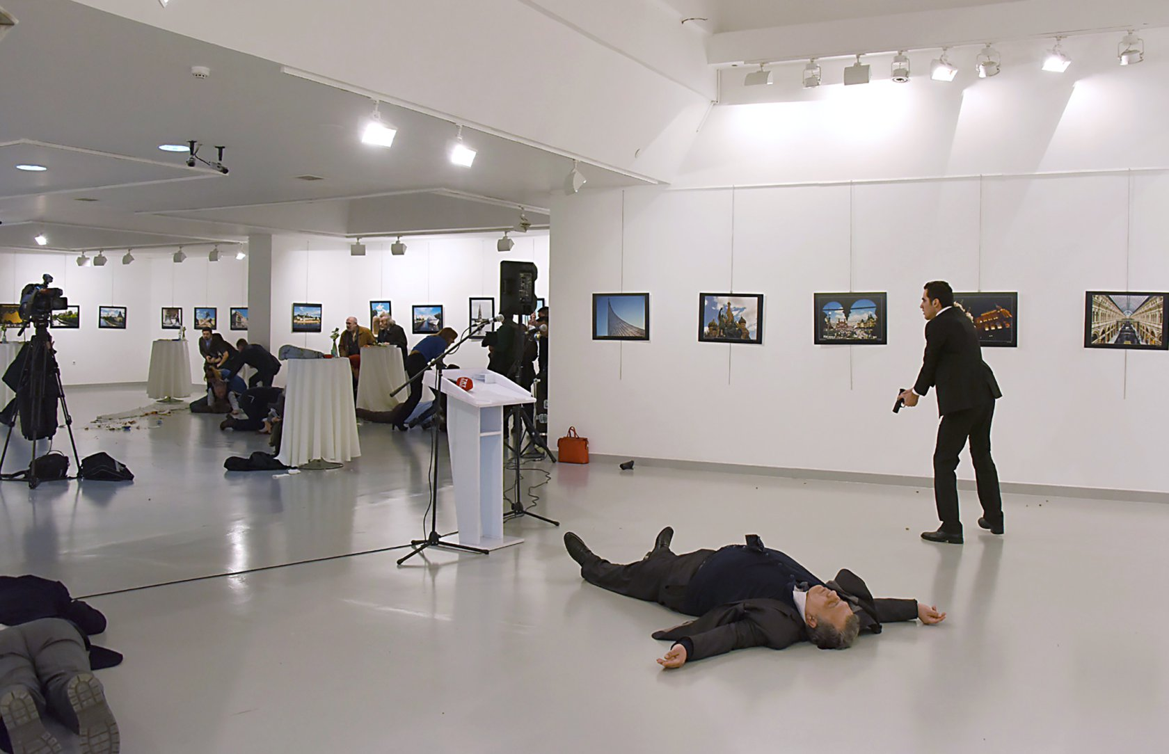 """TOPSHOT - EDITORS NOTE: Graphic content / This picture taken on December 19, 2016 shows Andrei Karlov (2ndR), the Russian ambassador to Ankara, lying on the floor after being shot by Mevlut Mert Altintas (R) during an attack during a public event in Ankara. A gunman crying """"Aleppo"""" and """"revenge"""" shot Karlov while he was visiting an art exhibition in Ankara on December 19, witnesses and media reports said. The Turkish state-run Anadolu news agency said the gunman had been """"neutralised"""" in a police operation, without giving further details. / AFP / Sozcu daily / Yavuz Alatan (Photo credit should read YAVUZ ALATAN/AFP/Getty Images)"""